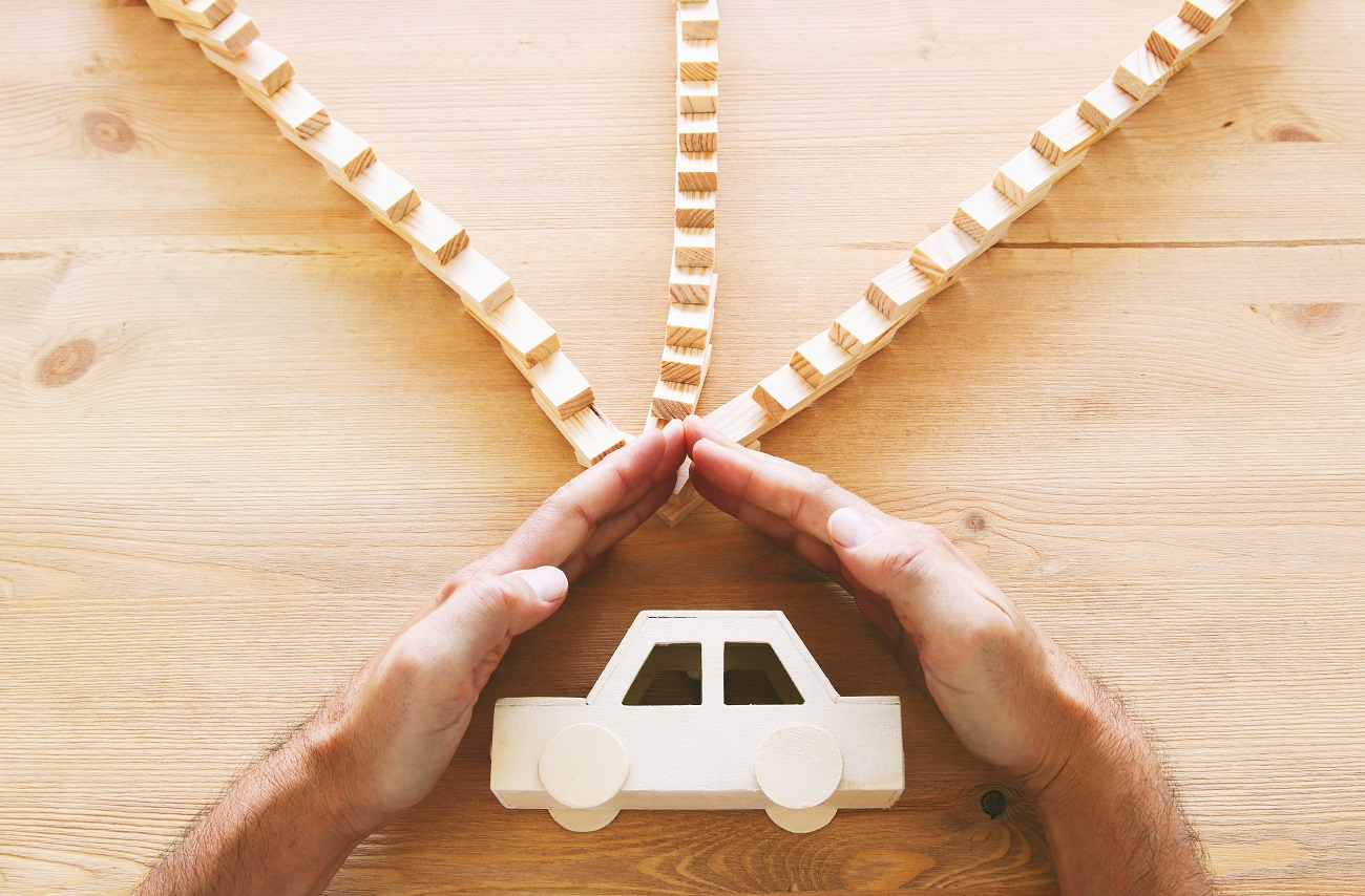 Hand sheltering car from falling dominoes