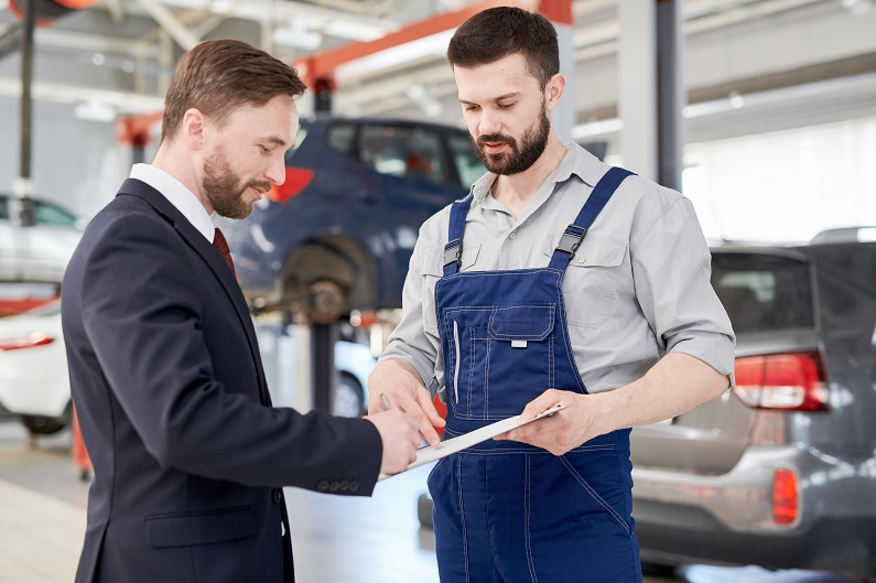 Businessman signing paperwork with mechanic